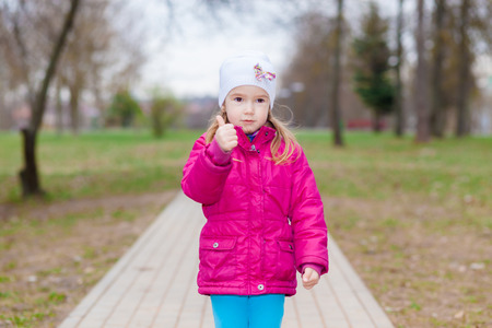 Young girl puts her big thumbs up. Portrait of cheerful kid. Smiling girl having fun outside. Happy successful person.