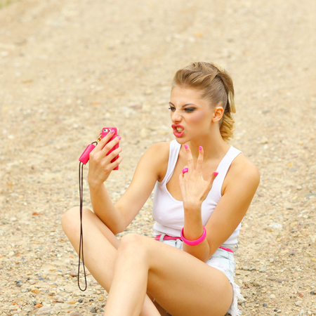 hipster girl in shorts and t-shirt sitting on the ground and makes selfie