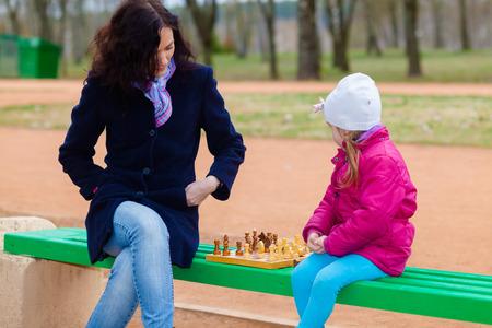 Prodigy: Matka i córka gra w szachy na ławce na zewnątrz w parku