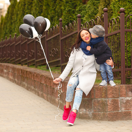 Portrait of fashionable baby boy and his gorgeous mother. little boy hugs his mother emotionally.