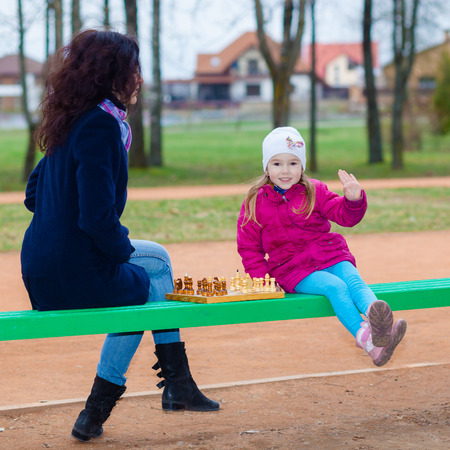Prodigy: Mother and daughter playing chess on a bench outdoors in park Zdjęcie Seryjne