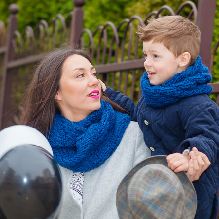 Portrait of fashionable baby boy and his gorgeous mother among balloons. little boy hugs his mother emotionally. Stock Photo