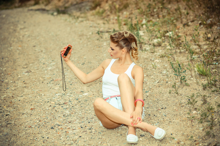 brash: hipster girl in shorts and t-shirt sitting on the ground and makes selfie