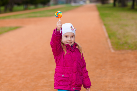 sucking lollipop: portrait of young funny little girl with lollipop. Young girl sucking lollipop. Outdoors, lifestyle. positive and cheerful  little girl