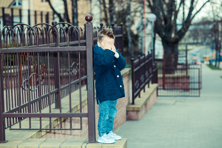 dreaminess: happy little Boy, outdoor. Trendy little boy covers his face