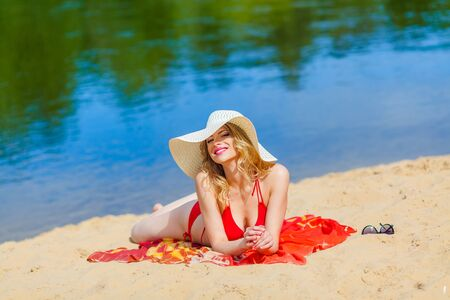 sexual position: girl in a red bikini sunbathing on the beach. Sexy blonde woman sunbathing by the sea