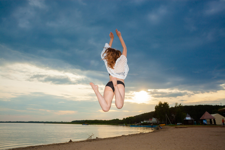 girl jumping on the beach at sunset background. Happy girl jumping on the beach on the dawn time. The concept of freedom and joy Stock Photo