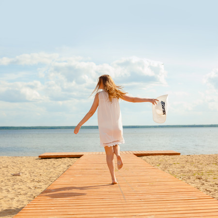Romantic girl in a white dress with a white hat turned to the long-tailed wooden pier on the beach. The concept of joy and happiness Stok Fotoğraf