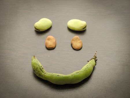 Close up of smile broad beans with wooden background. Make smiley shape with green fresh broad beans and dry broad beans and green bean pod on black table.