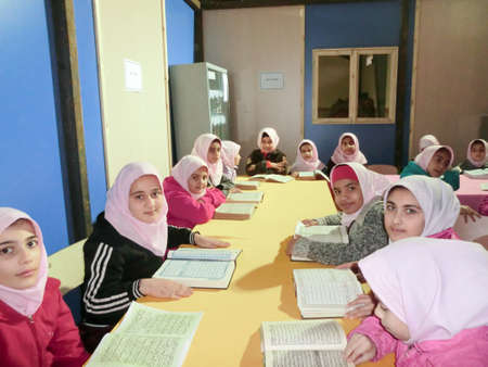 Primary school girls Studying book.An Islamic school where girls should wear scarves and dress uniforms