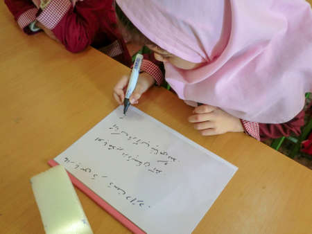 One of the primary school girls in Rasht, Guilan province, Iran. An Islamic school where girls should wear scarves and dress uniforms Éditoriale