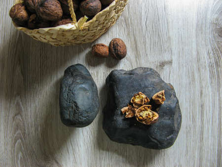 Fresh organic walnuts are  into a wicker basket next to Walnuts broken on the stone on wooden table. Whole Ripe walnut kernels. Close up. Top view. Healthy lifestyle. Vegan food.