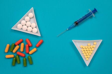 Multicolored pills are scattered on the table, syringe, needle. Top view with copy space, flat lay.