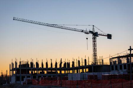 Industrielle Baukräne und Gebäudesilhouetten auf einer Baustelle im Hintergrund bei Sonnenuntergang oder Morgendämmerung. Standard-Bild