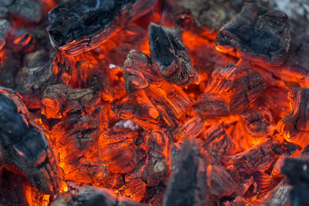 Flame incinerates firewood and transforms it ashes, close up, shallow depth of field. Blaze in a large stove. Nature texture of fire. The flame of fire burns in the brazier, smoldering firewoods. 스톡 콘텐츠