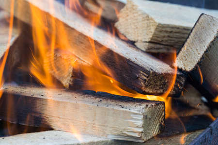 Flame incinerates firewood and transforms it ashes, close up, shallow depth of field. Blaze in a large stove. Nature texture of fire. The flame of fire burns in the brazier, smoldering firewoods. Stock Photo