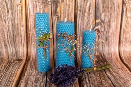 Blue honey candles handmade from natural wax on a background of wooden boards. Elements from natural materials. Christmas or New Years composition. Photo for postcards.