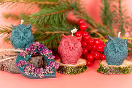 Handmade honey candles made of natural wax in the form of owls on a pink background. Elements from natural materials. Christmas or New Year composition. Photo for postcards. High quality photo