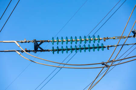 New large mast of an air power line close up, high voltage electricity pylon with thick wires and insulators, blue sky on background. Traditional energy. Electric power concept.