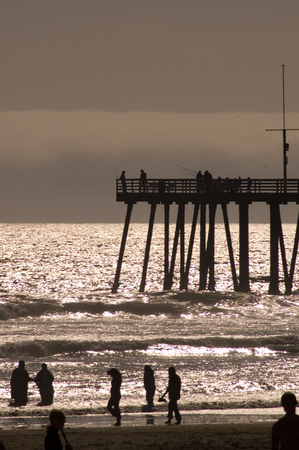 magic hour: Pier on a Californian beach at sunset with people walking