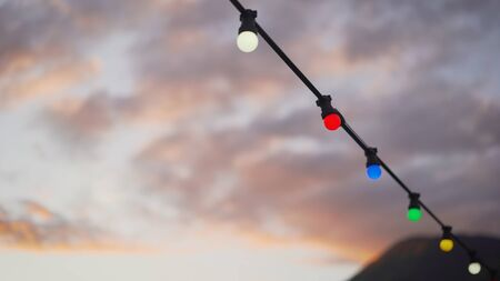 Garland on a background of sunset and mountains. Elements of the beach wedding decoration, parties. Lamps and hearts hung on a rope against the sea.