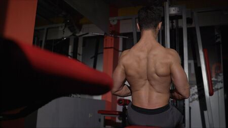 very power athletic guy bodybuilder, execute exercise with gym apparatus, on broadest muscle of back. back workout in the gym.