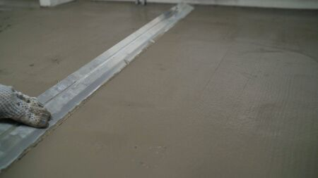 Floor leveling. Filling the floor with a self-leveling compound. Worker spreads the floor with mortar