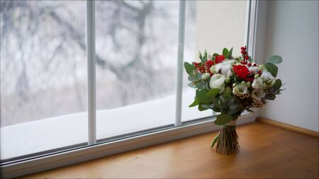 bright red wedding bouquet of fresh flowers and eucalyptus stands on the windowsill. Beautiful wedding bouquet on the windowsill.