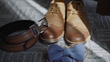 Close up of brown leather male shoes, bow tie, belt and camera on wooden background. Modern man or groom accessories. Wedding details. Male casual outfits. Top view, flat lay. Fees the groom. The morning of the groom. Boots, butterfly, belt Banco de Imagens - 140707955