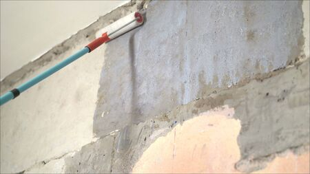 Applying a primer on the wall.. Long handle roller brush applying white primer paint on concrete wall with glass blocks in part of door frame, building and home renovation concept Stock Photo