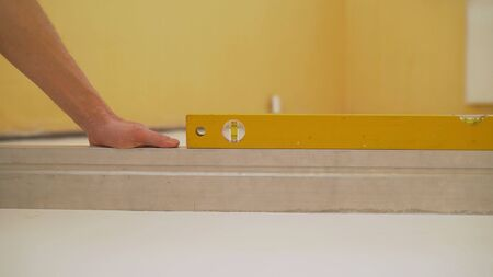 A worker checks the floor level using a tool level. Smooth White Floor Test Tool
