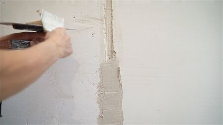 plaster application on the wall. Decorative plaster coating. Man does ragged texture on the wall using a spatula.