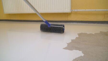 Needle roller for bulk floors. finishing work - the worker does the bulk floor Archivio Fotografico
