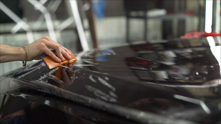 Master glues a protective film on the hood of the car. professional applying protective film to the red car 免版税图像