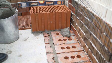 Ceramic blocks. Worker puts a red ceramic block. Building a house from a red ceramic block. damaged ceramic block of orange color