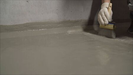 The process of waterproofing the floor with a solution. Workers cover the concrete screed with mortar and make waterproofing. Stock Photo