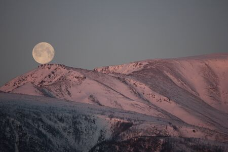 Big moon over a snowy mountain. Night replaces the full moon day. Big moon against the backdrop of snow-capped mountains.
