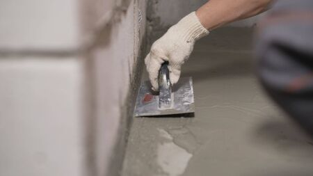 An industrial worker at a construction site installs a sealant for waterproofing cement. Worker puts liquid foil on a concrete floor. Workers applying the memory form of polymer waterproofing. Waterproofing the leveling floor with a spatula.