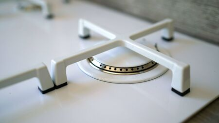 Macro closeup of modern luxury gas stove top with tiled backsplash. White modern gas stove