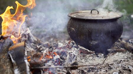 Cooking traditional soup over an open fire in the forest. Bonfire picnic in the forest. A pot of soup cooked over a fire.