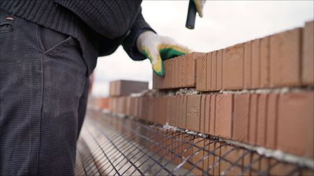 The construction of walls made of expensive red bricks. Professional bricklaying during the construction of a house.