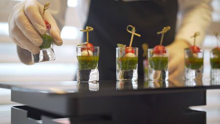 Catering. The waiter lays out snacks. off-premise catering - waitresses put fruit canapes on buffet table Фото со стока