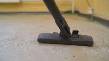 Un ouvrier nettoie des locaux industriels. appartement après réparation à l'aide de polysos. Un travailleur à l'aide d'un aspirateur enlève les débris de construction.