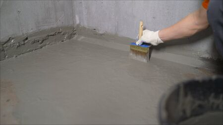 The master puts waterproofing on a concrete floor with a brush. Waterproofing concrete mortar.
