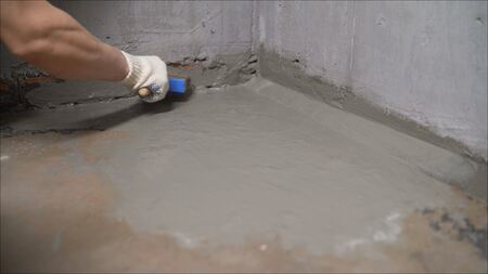 The master processes the floor with a brush. Waterproofing the floor with a brush and mortar. Flooring waterproofing.