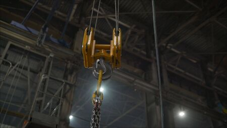 Crane in the factory lifts metal sheets. Low angle view of manual worker operating crane lifting sheet metal in industry