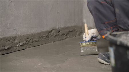 A worker applies waterproofing to a concrete floor with a brush. Concrete floor repair. Waterproofing mortar on a concrete floor.