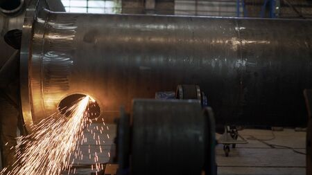 Heavy industry worker cuts a huge pipe. Work grinder cuts metal at the factory.