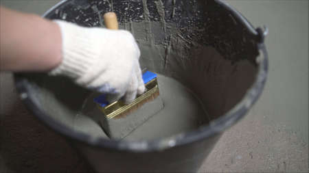 An industrial worker at a construction site installs a sealant for waterproofing cement. Worker puts liquid insulation on the floor. Workers applying the memory form of polymer waterproofing. Waterproofing concrete floor with mortar and brush.