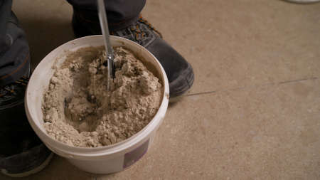 tile adhesive mixture in yellow bucket. Stir the tile adhesive in a bucket